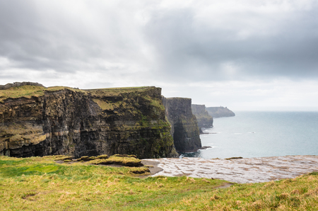 moher: These are the Cliffs of Moher in Ireland under a bluish cloudy sky.