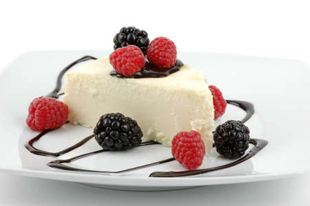 Creamy traditional cheesecake with berries and chocolate sauce. Stok Fotoğraf