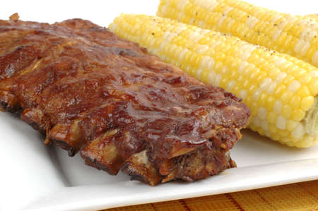 Rack of delicious ribs with corn on the cob.