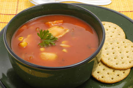 satisfying: Bowl of hearty vegetable soup and crackers. Stock Photo