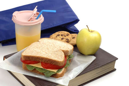 School lunch of sandwich, juice and snacks on a textbook.