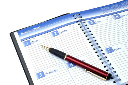 Datebook and pen on a white background.