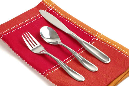Silver eating utensils on a colorful  linen napkin. Imagens
