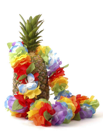 Colorful lei draped over a fresh pineapple. Stock Photo