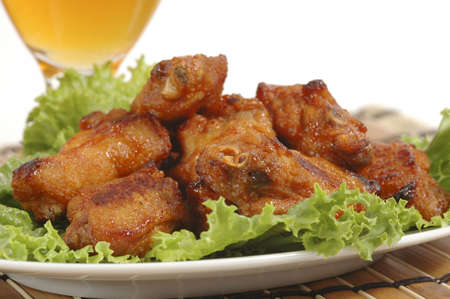 Closeup of barbecued chicken wings on a bed of lettuce. Imagens