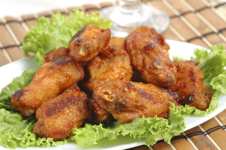 Spicy hot barbecued wings on bed of lettuce.