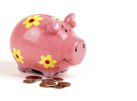 Pink ceramic piggy bank with loose coins around.