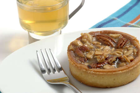 sugary: Butter tart made with assorted nuts served with tea. Stock Photo