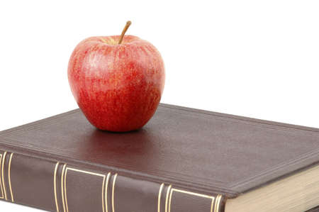 Red apple sitting on a book.