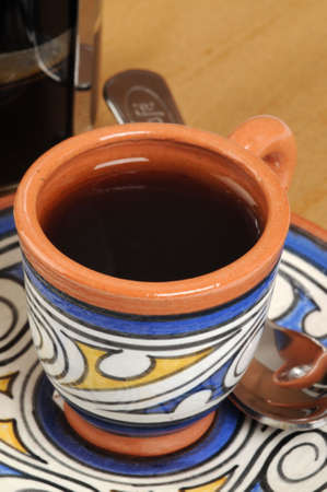 brewed: Cup of freshly brewed coffee in colorful pottery mug.
