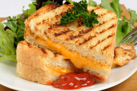Lekkere gegrilde boterham met kaas geserveerd met salade greens. Stockfoto