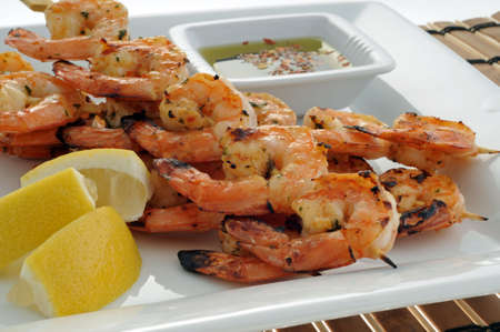 Delicious grilled shrimp with lemon and dipping sauce. Imagens