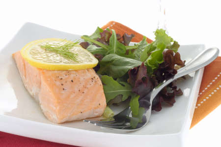 poached: Delicious poached salmon served with greens and lemon. Stock Photo