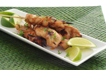 Grilled chicken satay served with lime wedges. Imagens - 3334374