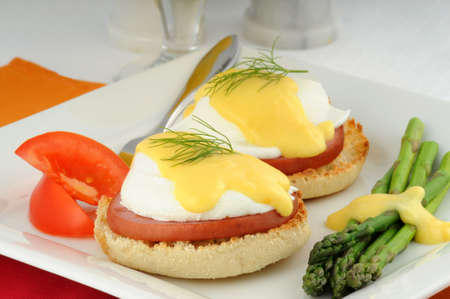 Delicious eggs benedict served with fresh vegetables.