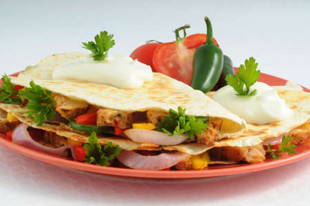 Delicious cheese and chicken quesadillas with sour cream. Imagens