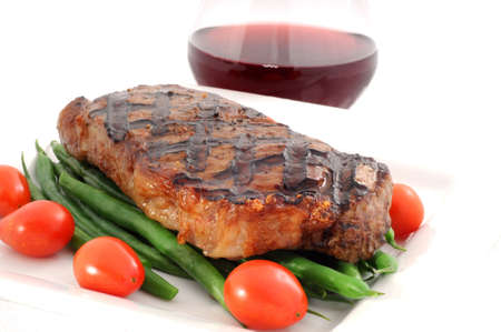 Ribeye steak grilled to perfection with green beans.