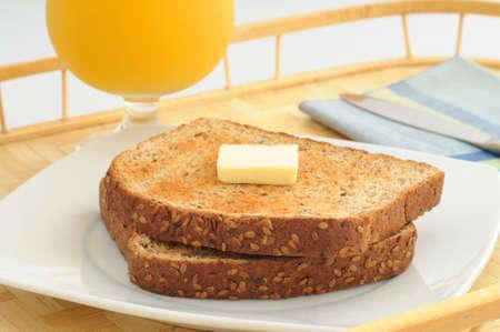 Wholegrain toast and butter served with orange juice. Reklamní fotografie