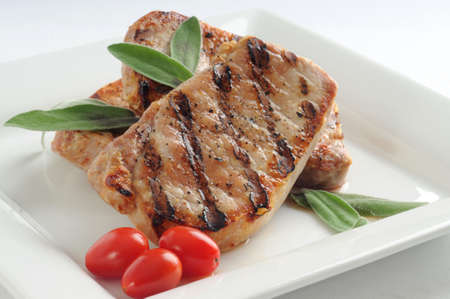 Juicy pork chop grilled and garnished with sage. Stock Photo