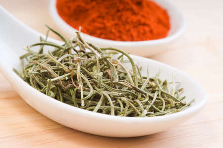 Aromatic dried rosemary in a white spoon.