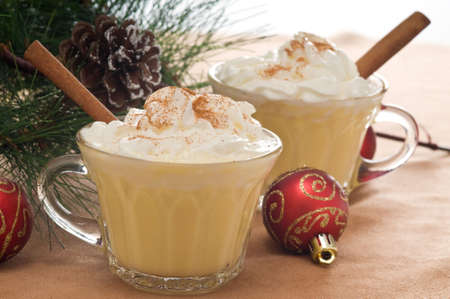 Festive drink of eggnog with whipped cream and cinnamon.