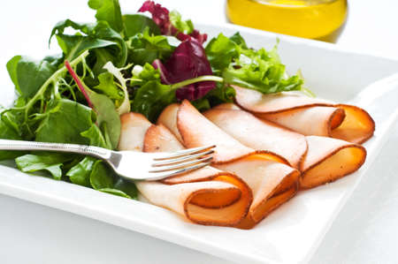Plate of prepared meats served with fresh salad greens. Imagens