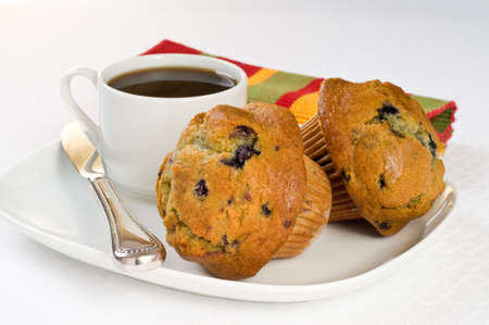 Fresh baked blueberry muffins served with coffee.