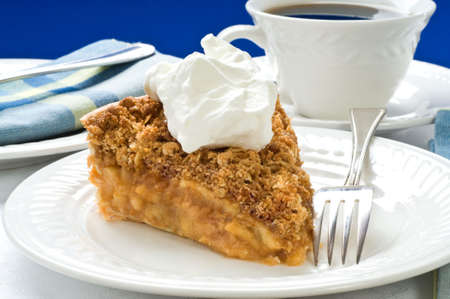Slice of apple pie with crumble topping and whipped cream. Imagens