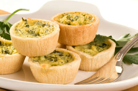 Delicious and homemade small quiche on a plate.