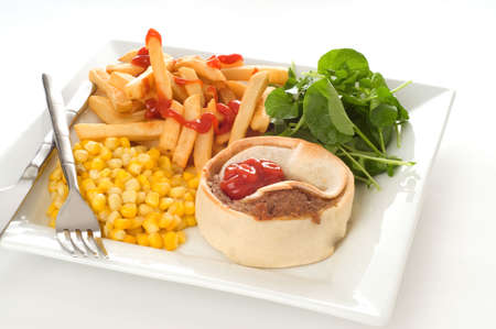 Homemade beef meat pie with fries and vegetables.