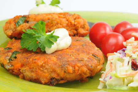 Delicious homemade salmon burgers served with vegetables.