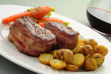 Bacon wrapped filet mignon served with potatoes and carrots. Imagens - 5039172