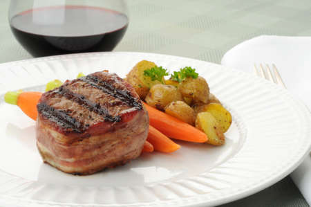 Grilled bacon wrapped steak with carrots and potatoes. Imagens