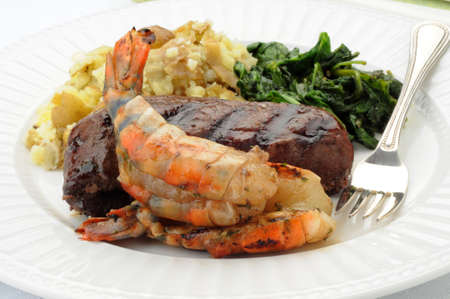 Shrimp and steak perfectly grilled on a white plate. Imagens