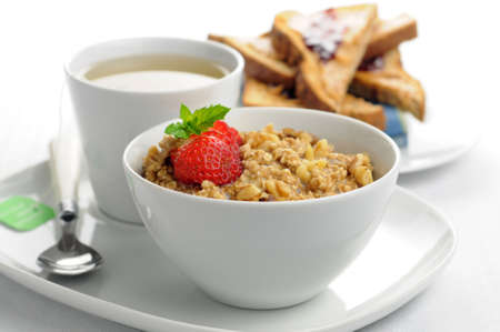 breakfast cereal: Delicious healthy oatmeal with a cup of tea and toast.