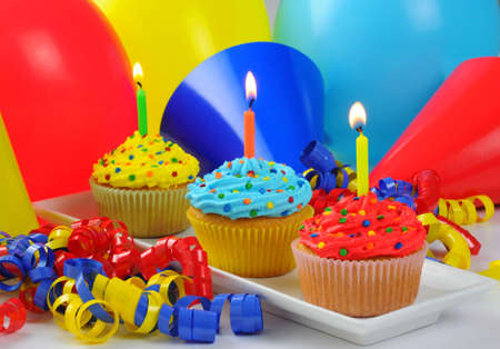 Colorful birthday cupcakes with lit candles. Imagens - 5411439