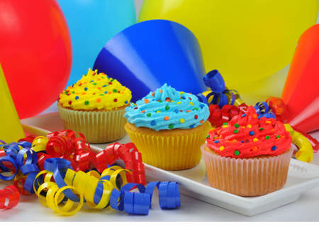 Colorful cupcakes placed with birthday balloons and hats. Imagens - 5411437