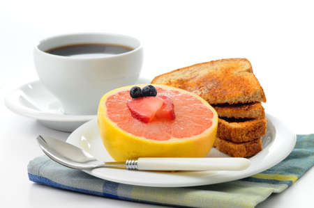 Half grapefruit served with toast and coffee.