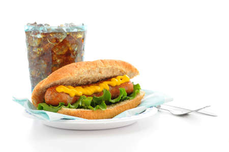 Grilled sausage on a bun with soft drink.