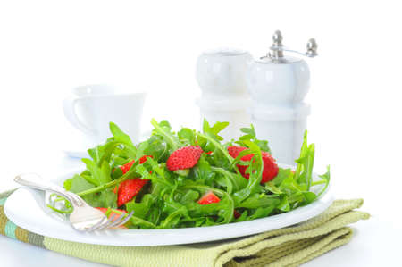 Fresh salad of arugula and strawberries with vinaigrette.