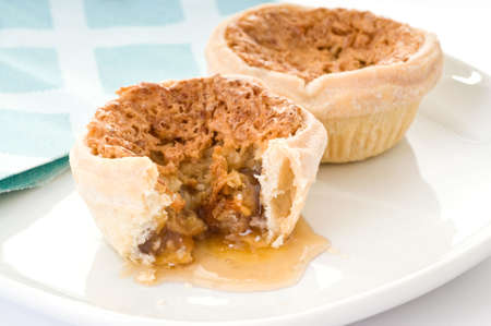 runny: Homemade butter tarts with runny filling on plate.