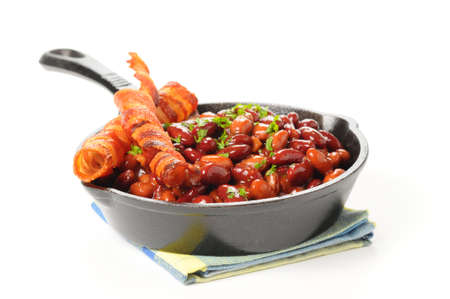 Baked beans and bacon served in a cast iron skillet. Stock Photo