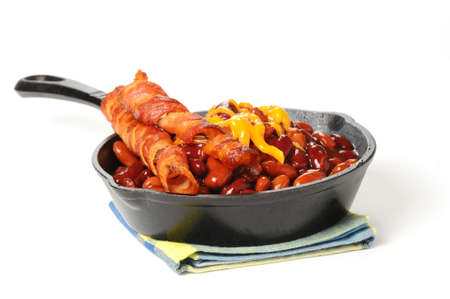 bacon baked beans: Baked beans and bacon served in a cast iron skillet. Stock Photo