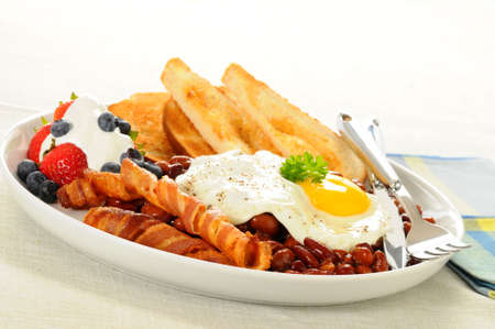 目玉焼き、ベーコンと豆のボリュームたっぷりの朝食。
