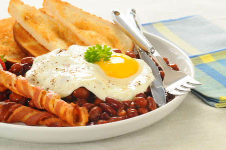 Fried egg with bacon, toast and beans.