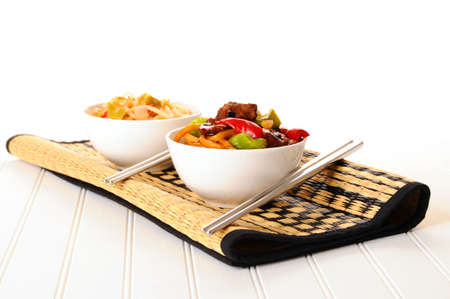 Bowls of delicious chinese food on a bamboo mat.