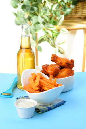 Crispy sweet potato fries served with baked chicken wings and beer. Imagens - 8534262