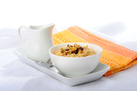 Bowl of hot oatmeal with raisins and walnuts.