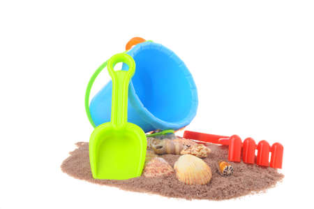 Colorful beach toys in the sand with sea shells. Stok Fotoğraf