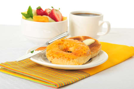 Toasted cheese bagel served with fresh fruit and coffee. Imagens